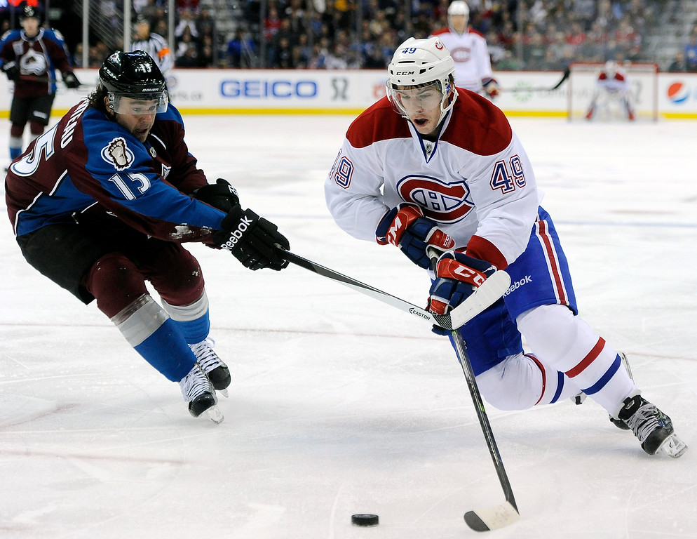 . Montreal Canadiens left wing Michael Bournival, right, brings the puck upice against Colorado Avalanche right wing P.A. Parenteau, left, in the second period of an NHL hockey game on Saturday, Nov. 2, 2013, in Denver. The Avalanche won 4-1. (AP Photo/Chris Schneider)
