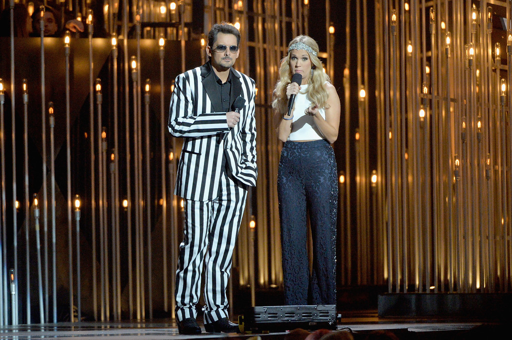 . NASHVILLE, TN - NOVEMBER 06:  Hosts Brad Paisley (L) and Carrie Underwood speak onstage during the 47th annual CMA awards at the Bridgestone Arena on November 6, 2013 in Nashville, United States.  (Photo by Rick Diamond/Getty Images)