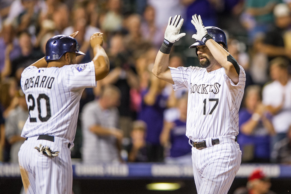 . DENVER, CO - AUGUST 30:  Todd Helton #17 of the Colorado Rockies celebrates his second three-run home run of the game for his 2,499th career hit with teammate Wilin Rosario #20 in the seventh inning of a game against the Cincinnati Reds at Coors Field on August 30, 2013 in Denver, Colorado. The Rockies beat the Reds 9-6. (Photo by Dustin Bradford/Getty Images)