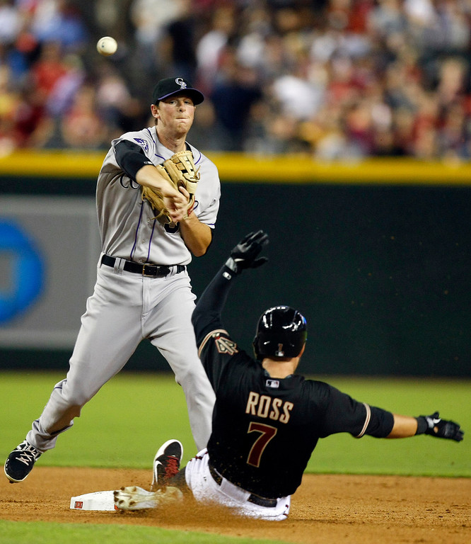 . Colorado Rockies second baseman DJ LeMahie, left, turns the double play while avoiding Arizona Diamondbacks Cody Ross, right, in the fifth inning during a baseball game on Friday, July 5, 2013, in Phoenix. (AP Photo/Rick Scuteri)