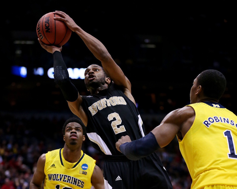 . Karl Cochran #2 of the Wofford Terriers shoots against Glenn Robinson III #1 and Derrick Walton Jr. #10 of the Michigan Wolverines in the second half during the second round of the 2014 NCAA Men\'s Basketball Tournament at BMO Harris Bradley Center on March 20, 2014 in Milwaukee, Wisconsin.  (Photo by Jonathan Daniel/Getty Images)