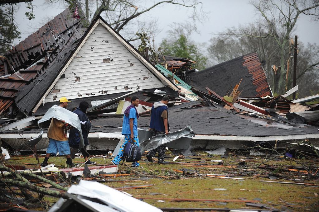 . Hattiesburg residents drag scrap metal through the yard of a destroyed home along Main Street in downtown Hattiesburg Miss., Feb. 11, 2013. A tornado swept through the area Sunday afternoon cutting a path of destruction through the city. (AP Photo/ Hattiesburg American, Ryan Moore)