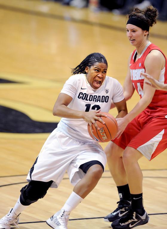 . Ashley Wilson of CU drives past Jourdan Ershine of New Mexico. Cliff Grassmick / December 29, 2012