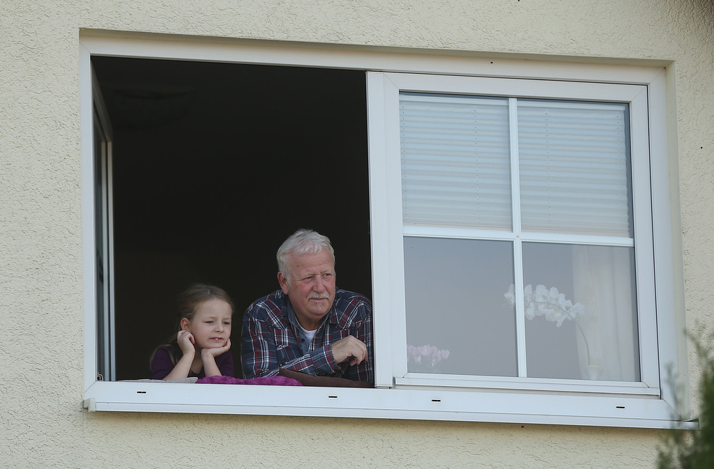 . An elderly man and his granddaughter watch from their upstairs window as actors arrive to re-enact The Battle of Nations on its 200th anniversary on October 20, 2013 near Leipzig, Germany. (Photo by Sean Gallup/Getty Images)