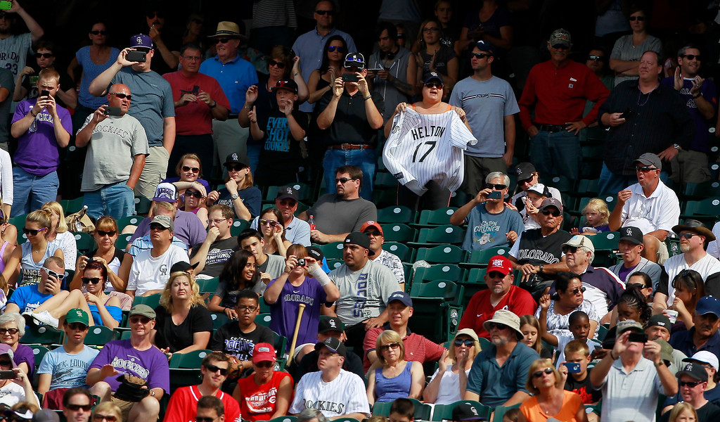 . Fans stand to watch Colorado Rockies\' Todd Helton bat against the Cincinnati Reds in the fourth inning of a baseball game in Denver, Sunday, Sept. 1, 2013. (AP Photo/David Zalubowski)
