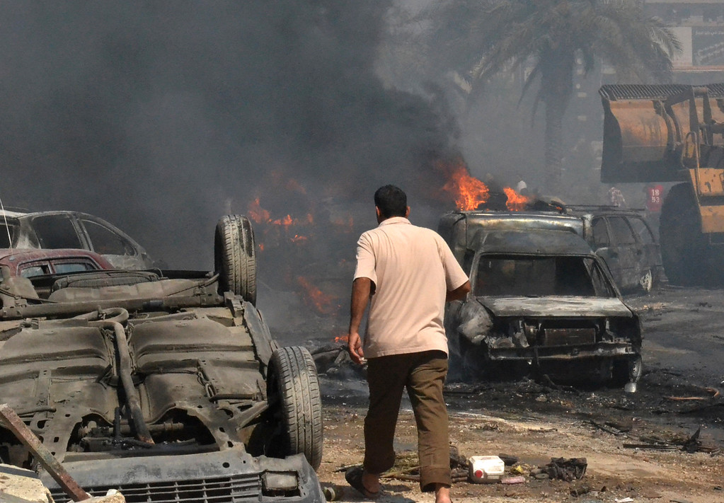 . A Lebanese man walks between damaged and burned cars at an explosion site outside of a mosque, in the northern city of Tripoli, Lebanon, Friday, Aug. 23, 2013.  (AP Photo)