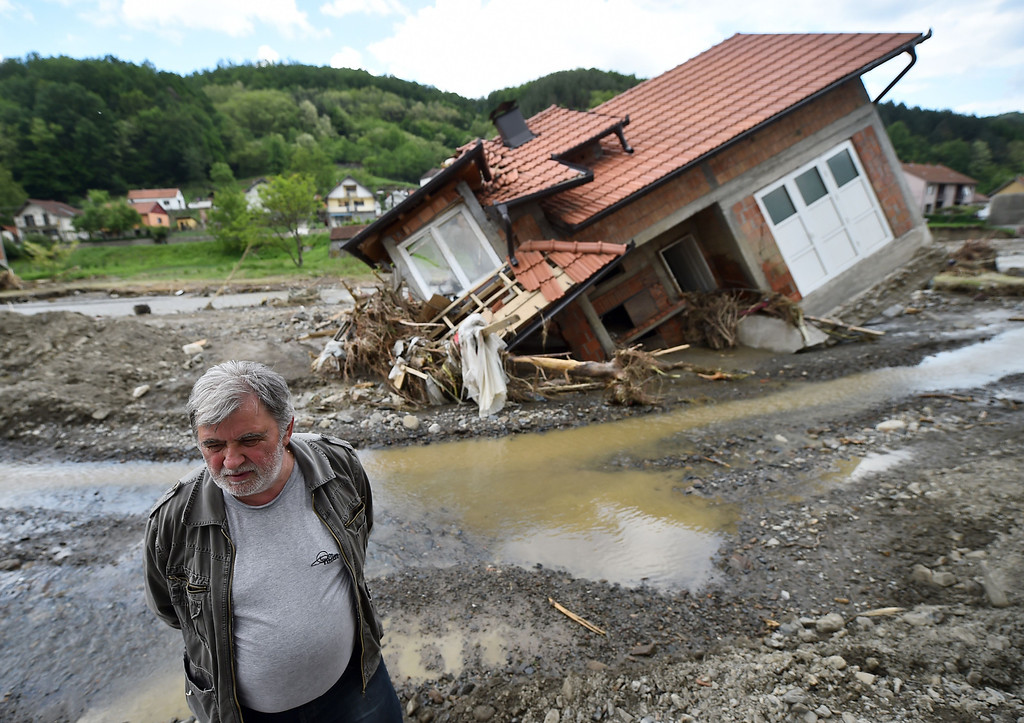 . A man stands near house damaged by flooding and landslides in Krupanj, some 130 kilometers south west of Belgrade, on May 20, 2014, after the western Serbian town was hit with floods and landslides, cutting it off for four days. Serbia declared three days of national mourning on May 20 as the death toll from the worst flood to hit the Balkans in living memory rose and health officials warned of a possible epidemic.  AFP PHOTO / ANDREJ ISAKOVIC/AFP/Getty Images