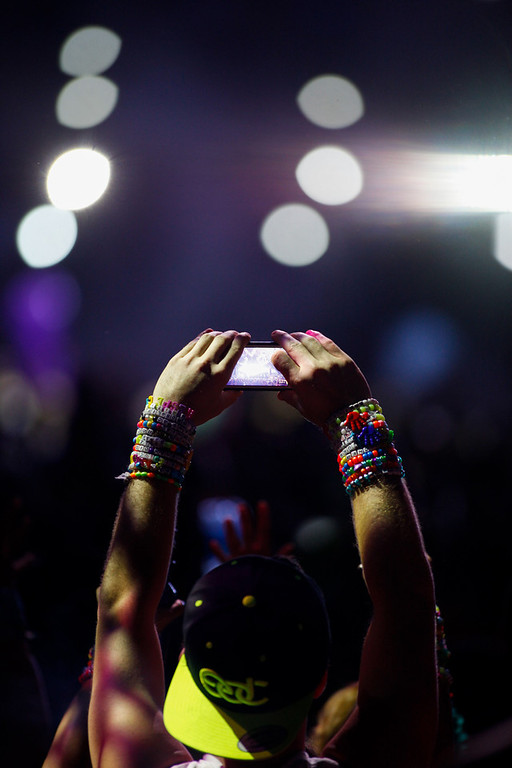 . In this Sunday, June 23, 2013 photo, an attendee records a video as Clockwork performs at the Circuit Grounds stage at the Electric Daisy Carnival at the Las Vegas Motor Speedway, in Las Vegas. (AP Photo/Las Vegas Review-Journal, Chase Stevens)
