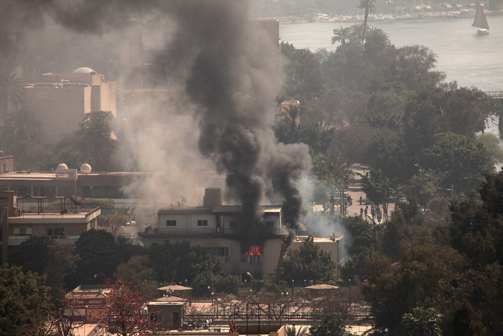 . Smoke and fire rises from the Egyptian Soccer Federation after protesters set fire following a court verdict in, Cairo, Egypt, Saturday, March 9, 2013. AP Photo/Maya Alleruzzo)