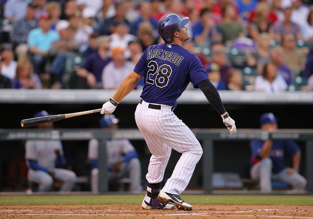 . Nolan Arenado #28 of the Colorado Rockies watches his two run home run off of starting pitcher Martin Perez #33 of the Texas Rangers to take a 2-0 lead in the second inning during Interleague play at Coors Field on May 5, 2014 in Denver, Colorado.  (Photo by Doug Pensinger/Getty Images)