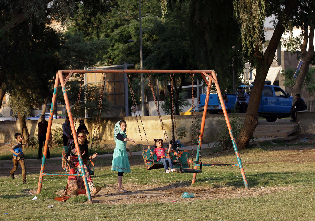 . Children play while Iraqi police stand guard at a park during the Muslim festival of Eid al-Adha in central Baghdad, Iraq, Tuesday, Oct. 15, 2013.  (AP Photo/Khalid Mohammed)