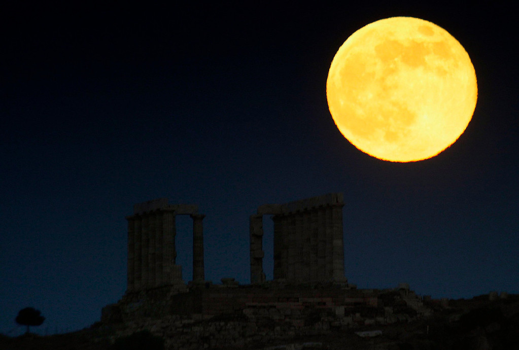 ". A ""super moon\"" rises over the temple of Poseidon, the ancient Greek god of the seas, in Cape Sounion some 37 miles east of Athens on June 23, 2013. On Sunday a perigee moon coincides with a full moon creating a \""super moon\"" when it will pass by the earth at its closest point in 2013.  REUTERS/Yannis Behrakis"