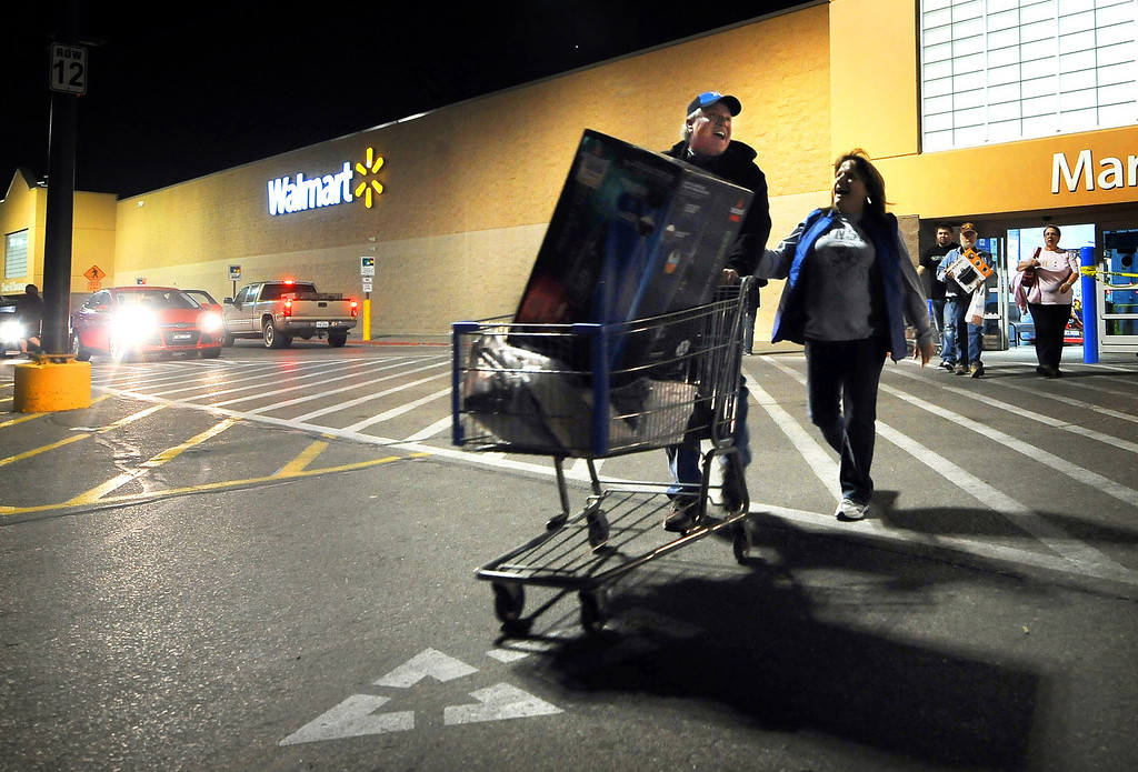 . Randy Wheeler, left, and his wife Nish, leave Wal-mart in Salina, Kan., Thursday evening Nov. 28, 2013, after purchasing a 60 inch TV that was on sale as part of a Black Friday promotion. (AP Photo/The Salina Journal, Tom Dorsey)