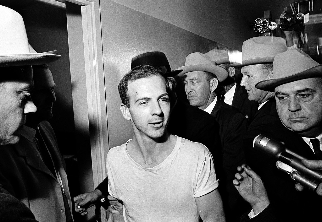 . Surrounded by detectives, Lee Harvey Oswald talks to the press as he is led down a corridor of the Dallas police station for another round of questioning in connection with the assassination of Kennedy on Nov. 23, 1963. Oswald, who denied involvement in the shooting, was formally charged with murder. Associated Press file