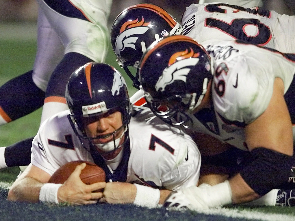 . Denver Broncos quarterback John Elway looks up after crossing the goal line in the fourth quarter of Super Bowl XXXIII in Miami, Sunday, Jan. 31, 1999. The Broncos defeated the Atlanta Falcons 34-19. At right is Broncos lineman Mark Schlereth. (AP Photo/Eric Draper)