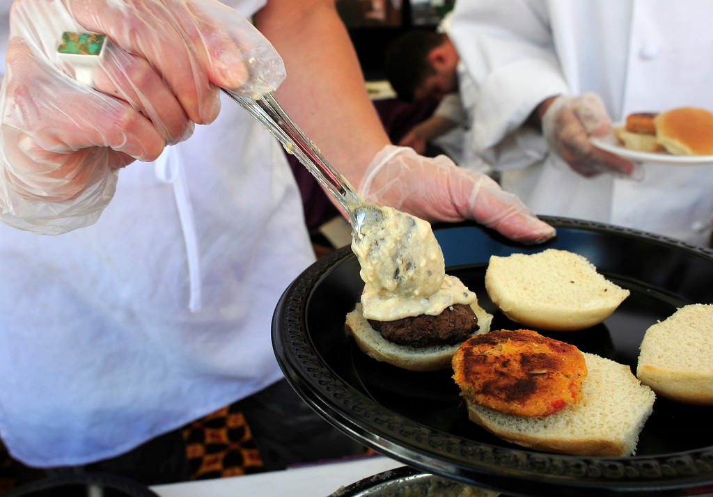 . Jill Klocek (L) and Rodolphe Lagoutte (R) prepare crab cake and beef sliders at the Randolph\'s booth during the A Taste of Colorado festival at Civic Center Park in Denver, Colorado, August 30, 2014. (Photo By Brenden Neville / Special to The Denver Post)