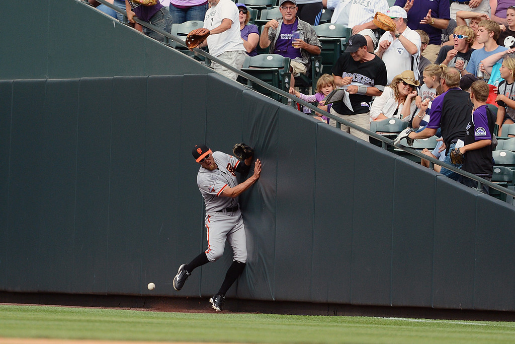 . Hunter Pence #8 of the San Francisco Giants runs into the outfield wall trying to catch a fly ball during the game against the Colorado Rockies from the dug out at Coors Field on June 30, 2013 in Denver, Colorado.  (Photo by Garrett W. Ellwood/Getty Images)