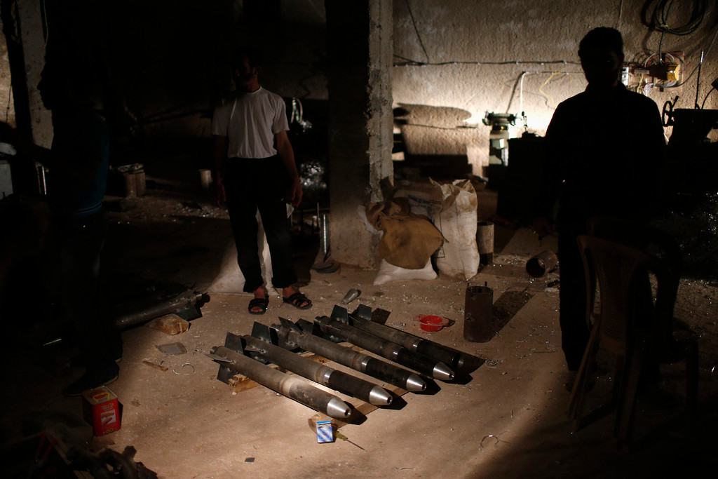 . Syrian rebel fighters stand around a cache of homemade missiles which they say they use on forces loyal to president Bashar al-Assad in Aleppo province August 21, 2012. The rebels say they get explosive materials from government shells which failed to explode.   REUTERS/Youssef Boudlal
