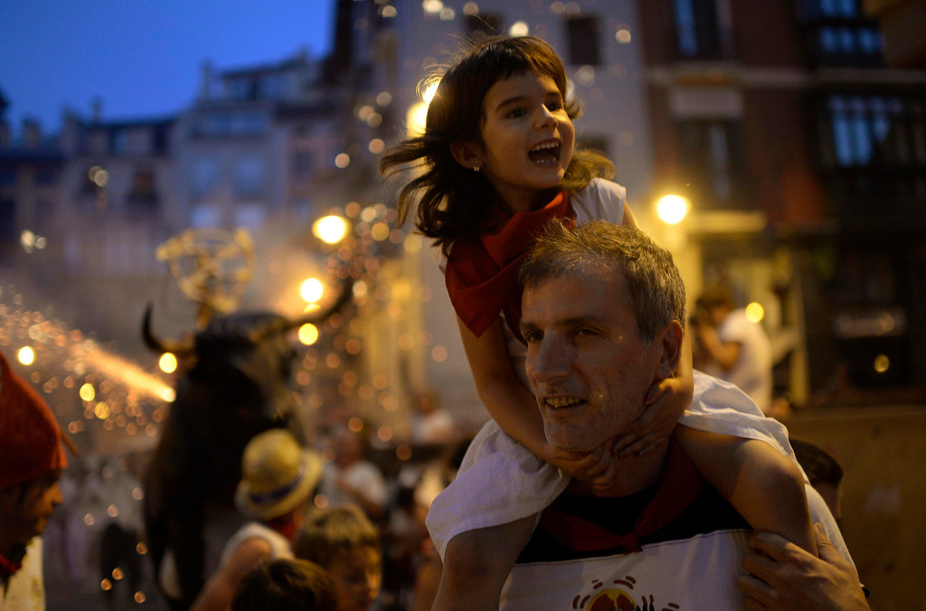 """. Revellers smile as sparks from the \""""Fire Bull\"""", a man carrying a metal structure loaded with fireworks, fly on the fourth day of the San Fermin festival in Pamplona July 9, 2013. Visitors to the nine-day festival, depicted in Ernest Hemingway\'s 1926 novel \""""The Sun Also Rises\"""", take part in activities including The Running Of The Bulls, an early morning half mile dash from the corral to the bullring alongside six bulls destined to die in the afternoon\'s corrida. This is followed by processions of giant traditional figures, concerts, firebulls, fireworks, and large doses of eating, drinking, dancing and late nights.  REUTERS/ Vincent West"""