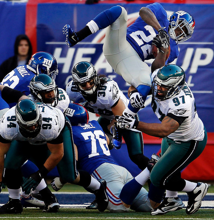 . New York Giants\' David Wilson, top right, is upended by Philadelphia Eagles\' Cullen Jenkins (97) on the goal line during the first half of their NFL football game, Sunday, Dec. 30, 2012, in East Rutherford, N.J. The Giants won 42-7. (AP Photo/The Philadelphia Inquirer, Ron Cortes)