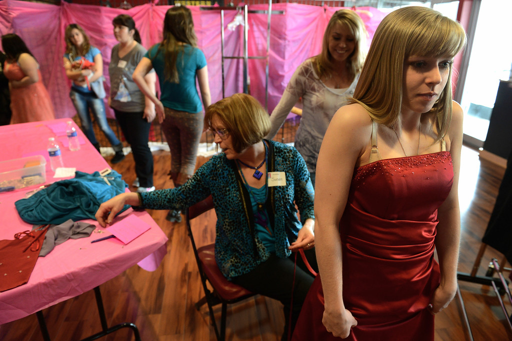 ". COMMERCE CITY, CO. - MARCH 16: Kersey Ruder, a senior at Green Mountain High School,   admires her dress while having alterations made by Susan Nixon during the Prom Dress Exchange Corp. event in Commerce City, CO March 16, 2013. With a valid student ID and a suggested $10 donation, teenage girls could chose from 1,356 donated dresses that lined a long hallway at Dick�s Sporting Goods Park.   Kersey\'s mother, Valerie Ruder, second from right, said, ""it\'s amazing. The girls can get a beautiful dress and not spend a million dollars. I love that they volunteer for alterations... they\'re kind people.\"" (Photo By Craig F. Walker/The Denver Post)"