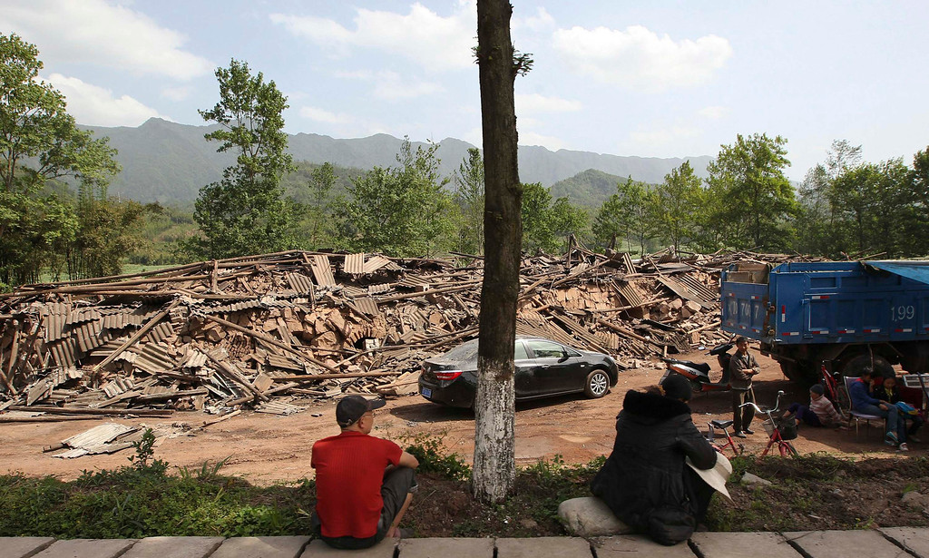 . People sit near collapsed buildings after a strong 6.6 magnitude earthquake, at Longmen village, Lushan county, Ya\'an, Sichuan province, April 20, 2013. The earthquake hit a remote, mostly rural and mountainous area of southwestern China\'s Sichuan province on Saturday, killing at least 102 people and injuring about 2,200 close to where a big quake killed almost 70,000 people in 2008. REUTERS/Stringer