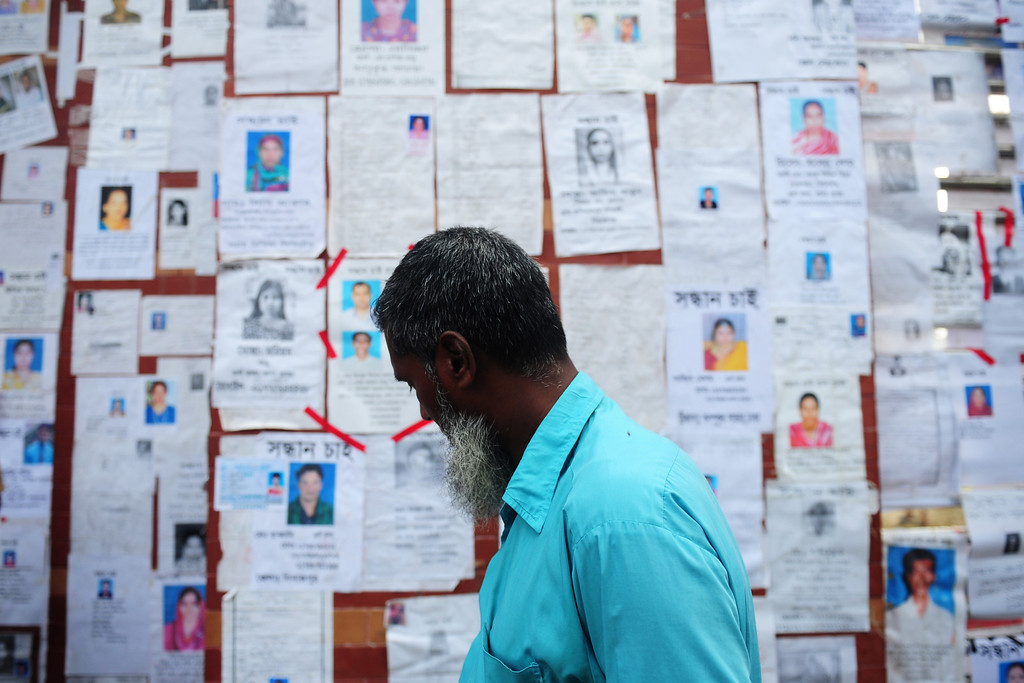 . A Bangladeshi relative looks at a board posting notices of missing and dead workers three days after an eight-storey building collapsed  in Savar, on the outskirts of Dhaka, on April 27, 2013. Police arrested two textile bosses over a Bangladeshi factory disaster as the death toll climbed to 332 and distraught relatives lashed out at rescuers trying to detect signs of life. MUNIR UZ ZAMAN/AFP/Getty Images