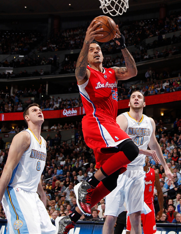 . Los Angeles Clippers forward Matt Barnes, front, slips between Denver Nuggets forward Danilo Gallinari, back left, of Italy, and center Kosta Koufos for a basket in the first quarter of an NBA basketball game in Denver, Thursday, March 7, 2013. (AP Photo/David Zalubowski)