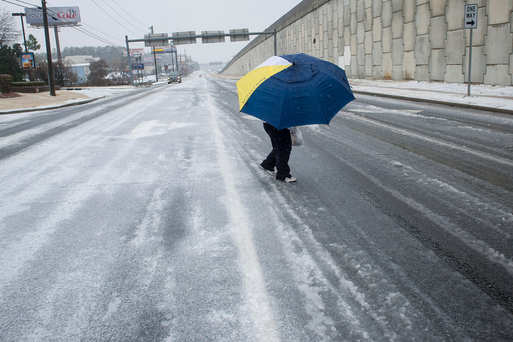 ". A woman uses an umbrella to shield herself from sleet while crossing an icy street during a winter storm on Wednesday, Feb. 12, 2014, in Doraville, Ga.  An ice storm gripped the winter-weary South on Wednesday and forecasters warned the worst of the potentially ""catastrophic\"" storm was yet to come.  (AP Photo/John Amis)"