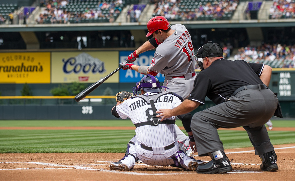 . Joey Votto #19 of the Cincinnati Reds grounds into a double play as Yorvit Torrealba #8 of the Colorado Rockies catches in the first inning of a game at Coors Field on September 1, 2013 in Denver, Colorado. (Photo by Dustin Bradford/Getty Images)