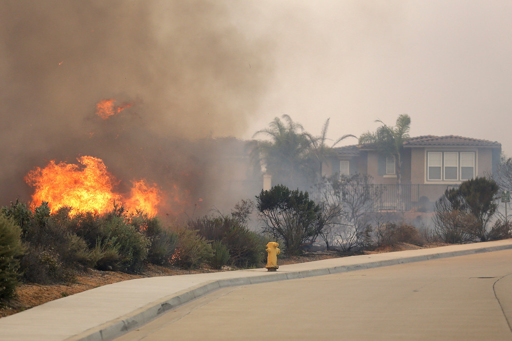 . A wildfire climbs a canyon toward homes Wednesday, May 14, 2014, in Carlsbad, Calif. More wildfires broke out Wednesday in San Diego County threatening homes in Carlsbad and forcing the evacuations of military housing and an elementary school at Camp Pendleton as Southern California is in the grip of a heat wave. (AP Photo)