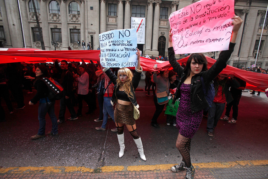 """. Two students hold up protest signs that read in Spanish; \""""The state does not regulate the business of prostitution because it is a \'private business.\'  If education is a private business, what can we expect?, \"""" during a student march demanding free education, in Santiago, Chile, Thursday, April. 11, 2013.  The marches began during the 2006-2010 Michelle Bachelet administration and have troubled President Sebastian Pinera even more. Pinera\'s government is focusing a chunk of the 2013 budget on financing school loans at lower rates. But students say the system still fails them, with poor public schools, expensive private universities, unprepared teachers and unaffordable loans. The(AP Photo/Luis Hidalgo)"""