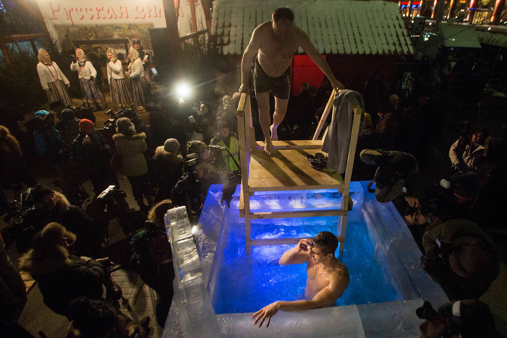 . A man crosses himself in the ice cold water, as another waits his turn to plunge in a small ice pool to mark Epiphany in the center of Moscow, next to Red Square, Russia, late Saturday, Jan. 18, 2014. The temperature in Moscow is -17C ( -1.4 F). Thousands of Russian Orthodox Church followers plunged into icy rivers and ponds across the country to mark Epiphany, cleansing themselves with water deemed holy for the day. Water that is blessed by a cleric on Epiphany is considered holy and pure until next year\'s celebration, and is believed to have special powers of protection and healing. (AP Photo/Denis Tyrin)