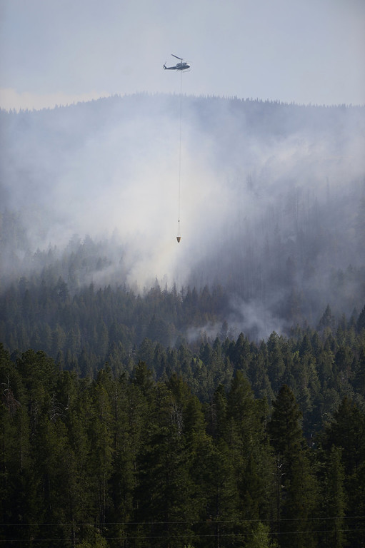 . A helicopter drops water on a fire burning in the hills west of Evergreen, Colorado. A fire started early in the afternoon on June 3, 2013 and by 3:30 p.m., residents of the surrounding area were told to evacuate. Many packed horses and other animals in trailers and drove them to nearby meadows. (Photo by AAron Ontiveroz/The Denver Post)