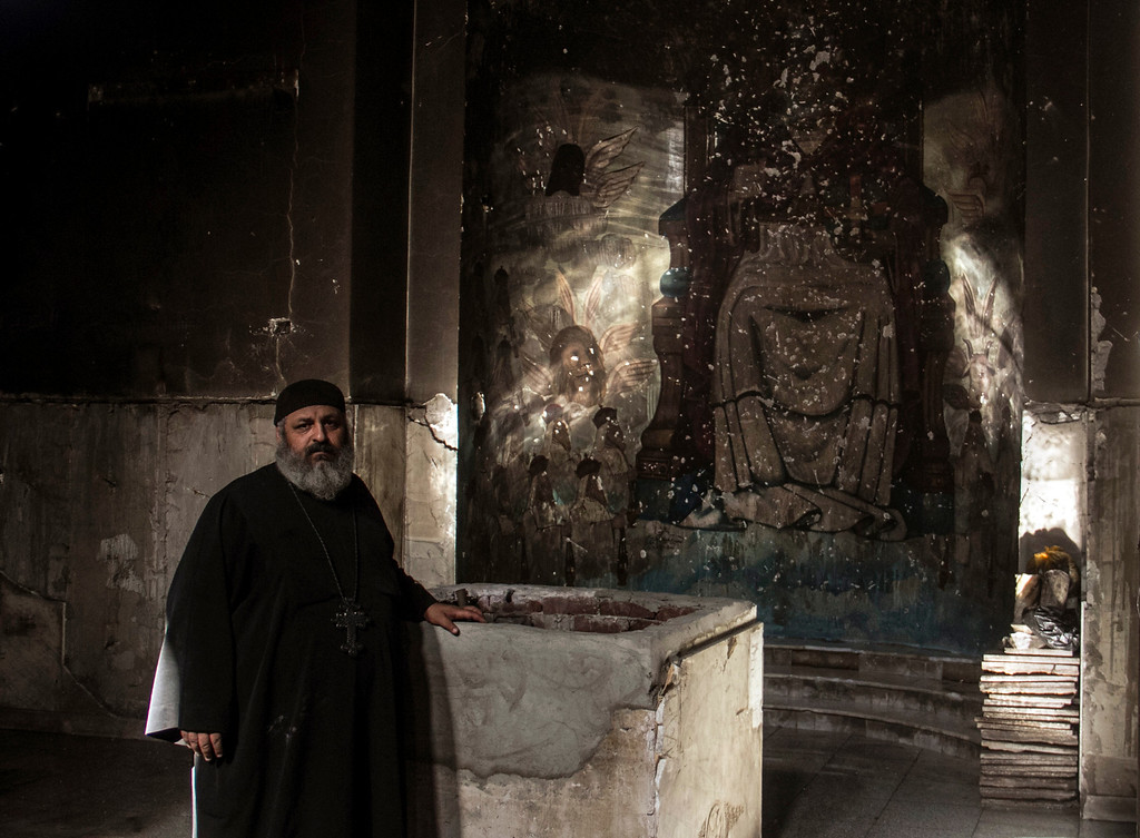 . In this Sept. 3, 2013 photo, Egyptian priest Ebrahim Tenisah, head of the main church, shows a visitor the damaged altar inside the Virgin Mary and St. Abraam Monastery that was looted and burned by Islamists, in Dalga, Minya province, Egypt. Dalga has been outside government control since hard-line supporters of the Islamist Mohammed Morsi drove out police and occupied their station on July 3, the day Egypt\'s military chief removed the president in a popularly supported coup. It was part of a wave of attacks in the southern Minya province that targeted Christians, their homes and businesses. (AP Photo/El Shorouk Newspaper, Roger Anis)