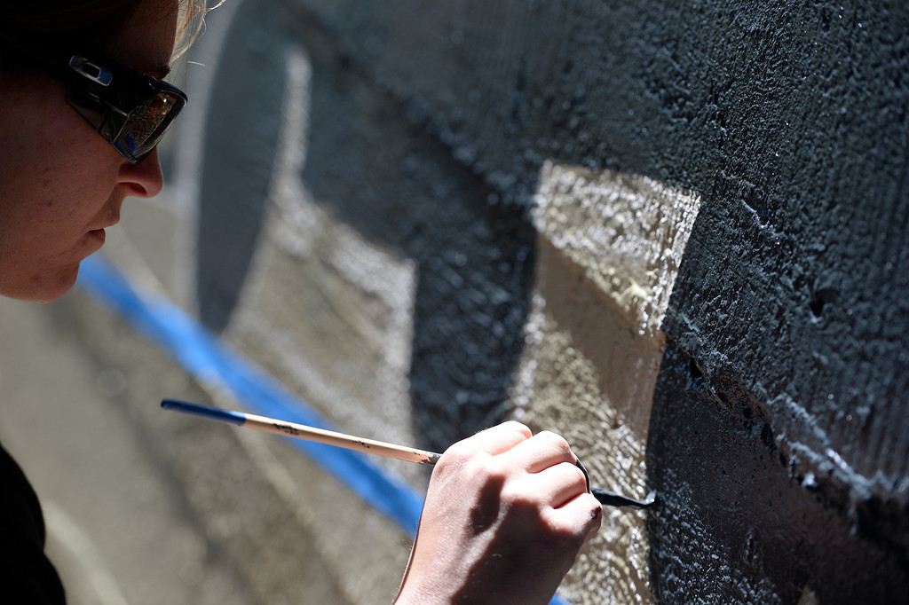 . Castle Rock is turning to murals as a way to discourage graffiti. Castle Rock police officer Renee Tremaine paints a train scene at Hangmans Gulch underpass June 9, 2014 along the Plum Creek trail.  (Photo by John Leyba/The Denver Post)st)
