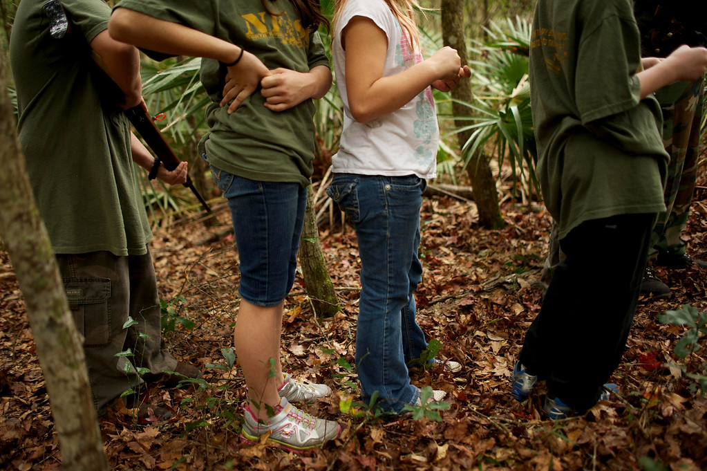 ". A group of children, all members of the North Florida Survival Group, walk through a wooded area during a field training exercise in Old Town, Florida, December 8, 2012. The group trains children and adults alike to handle weapons and survive in the wild. The group passionately supports the right of U.S. citizens to bear arms and its website states that it aims to teach ""patriots to survive in order to protect and defend our Constitution against all enemy threats\"". Picture taken December 8, 2013.   REUTERS/Brian Blanco"