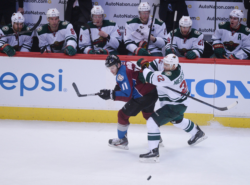 . Jamie McGinn (11) of the Colorado Avalanche grapples with Nino Niederreiter (22) of the Minnesota Wild during the first period of action.   (Photo by Karl Gehring/The Denver Post)