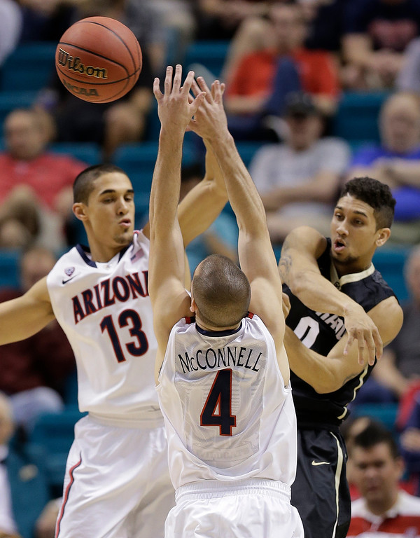 . Colorado\'s Askia Booker, right, passes off the ball against Arizona\'s Nick Johnson and Arizona\'s T.J. McConnell during the first half of an NCAA college basketball game in the semifinals of the Pac-12 Conference on Friday, March 14, 2014, in Las Vegas. (AP Photo/Julie Jacobson)