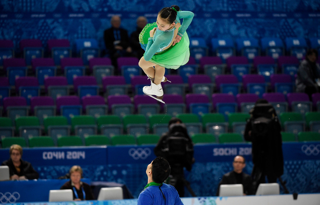 Description of . Peng Cheng from China is thrown by her partner Hao Zhang as they perform their short program in the pairs figure skating competition at the Sochi Winter Olympics Tuesday, Feb.11, 2014 in Sochi. (AP Photo/The Canadian Press, Paul Chiasson)