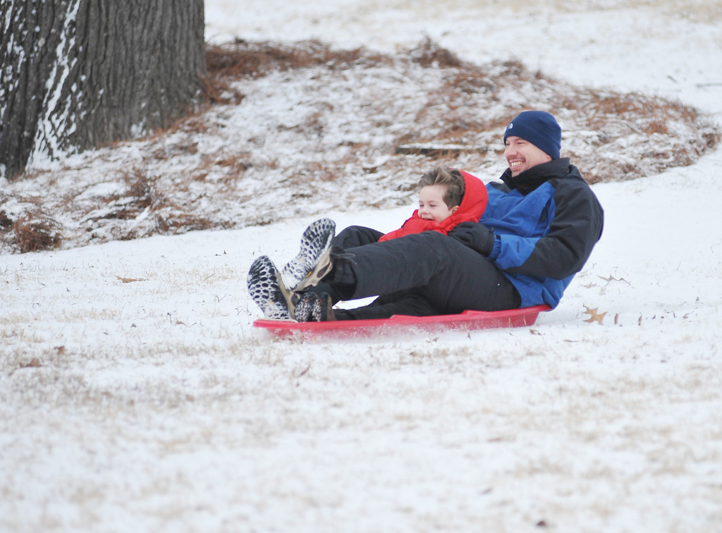. Scott Vasilyev, right, and his son Alex slide down a hill, in Oxford, Miss. on Tuesday, Feb. 10, 2014.  There is another chance of snow or sleet in northern Mississippi for Tuesday night, with low temperatures in the low to mid-twenties.  (AP Photo/Oxford Eagle, Bruce Newman)
