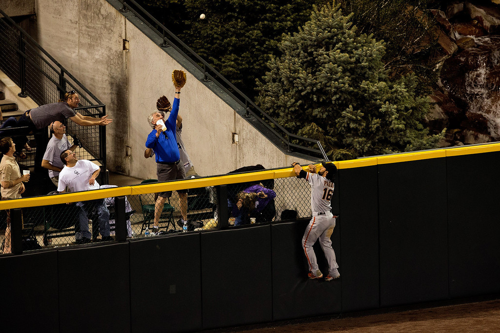 . DENVER, CO - MAY 17:  Center fielder Angel Pagan #16 of the San Francisco Giants climbs the wall and watches a solo home run by Carlos Gonzalez #5 of the Colorado Rockies (not pictured) fly over the fence during the sixth inning at Coors Field on May 17, 2013 in Denver, Colorado.  (Photo by Justin Edmonds/Getty Images)