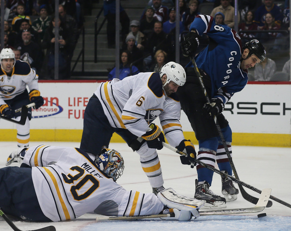 . Buffalo Sabres goalie Ryan Miller, left, makes a stick-save of a shot by Colorado Avalanche left wing Patrick Bordeleau, right, as Sabres defenseman Mike Weber covers in the second period of an NHL hockey game in Denver, Saturday, Feb. 1, 2014. (AP Photo/David Zalubowski)