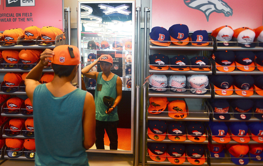 . Alex Tom, of Denver, tries on Broncos\' hats at the Denver Broncos Team store at of Sports Authority Field at Mile High  in Denver. Photo by Helen H. Richardson/The Denver Post
