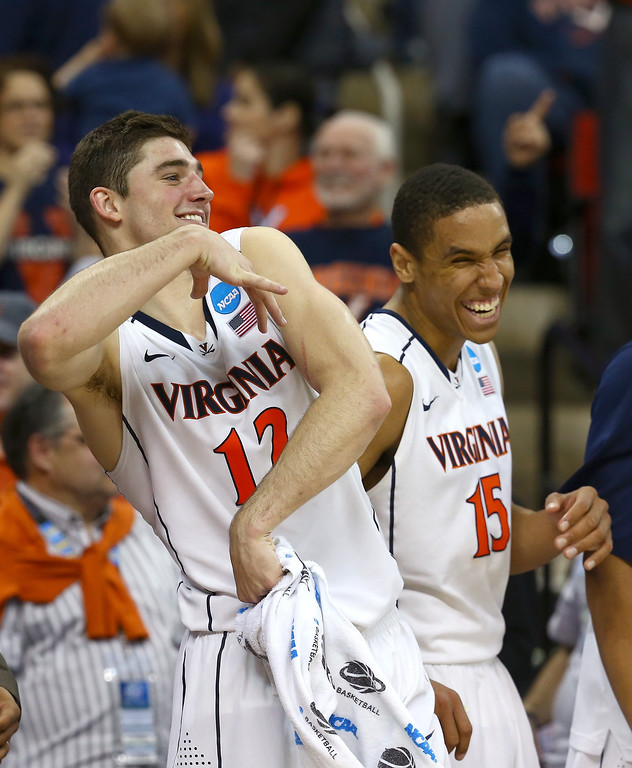 . Joe Harris #12 of the Virginia Cavaliers celebrates with Malcolm Brogdon #15 late in the game against the Memphis Tigers during the third round of the 2014 NCAA Men\'s Basketball Tournament at PNC Arena on March 23, 2014 in Raleigh, North Carolina.  (Photo by Streeter Lecka/Getty Images)