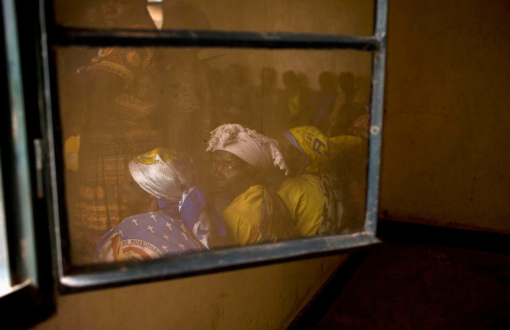 . Members of Congolese Women\'s Association, who have been widowed by conflict, are reflected in a window during their meeting in the town of Rutshuru in North Kivu, east of the Democratic Republic of Congo, May 23, 2012.  REUTERS/Siegfried Modola