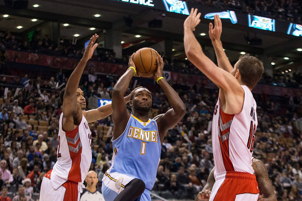 . Denver Nuggets\' Jordan Hamilton, center, shoots as Toronto Raptors\' Rudy Gay, left, and Steve Novak defend during the first half of an NBA basketball game on Sunday, Dec. 1, 2013, in Toronto. (AP Photo/The Canadian Press, Chris Young)