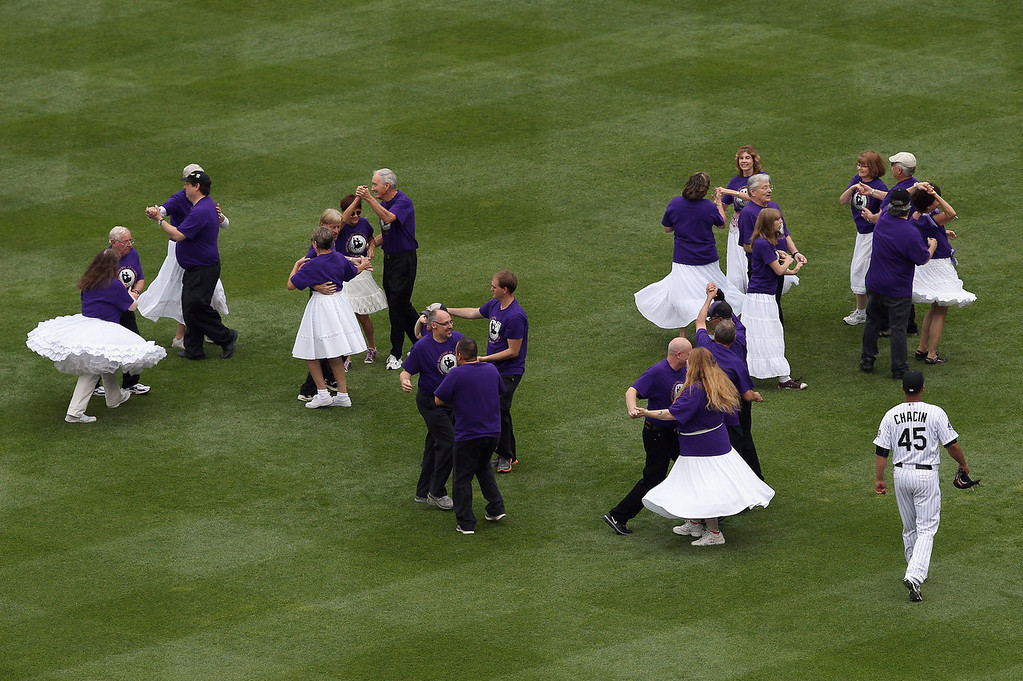 . Starting pitcher Jhoulys Chacin #45 of the Colorado Rockies walks past square dancers providing pregame entertainment as he heads to the bullpen to warm up prior to facing the Milwaukee Brewers at Coors Field on July 28, 2013 in Denver, Colorado.  (Photo by Doug Pensinger/Getty Images)