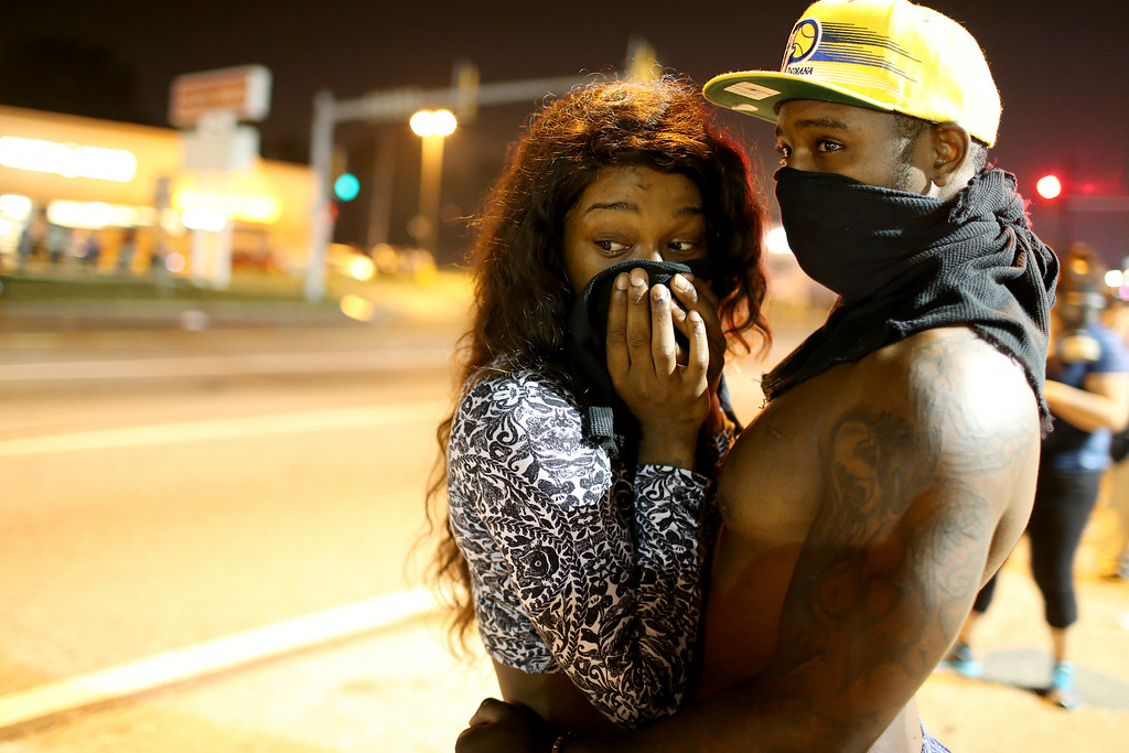 . FERGUSON, MO - AUGUST 18: Demonstrators  cover their faces as tear gas fills the air as police fire the gas against an unruly crowd protesting the shooting death of Michael Brown on August 18, 2014 in Ferguson, Missouri. Police sprayed pepper spray, shot smoke, gas and flash grenades as violent outbreaks have taken place in Ferguson since the shooting death of Michael Brown by a Ferguson police officer on August 9th.  (Photo by Joe Raedle/Getty Images)