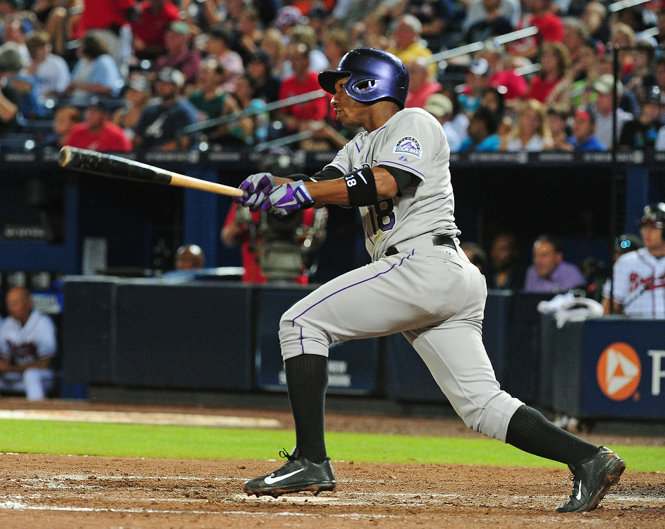 . Jonathan Herrera #18 of the Colorado Rockies hits a run scoring single in the 7th inning against the Atlanta Braves at Turner Field on August 1, 2013 in Atlanta, Georgia. (Photo by Scott Cunningham/Getty Images)